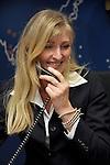 Jonge vrouw aan het werk, overlegt zittend aan aan bureau met telefoon in haar hand, met haar collega over de voortgang van een project