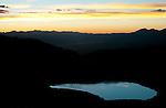 An alpine tarn reflects the evening light as sunset settles over the Gunnison Valley as viewed from Cottonwood Pass near Buena Vista, Colorado.