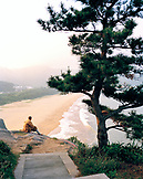 CHINA, Putou Shan, a monk sits by a tree with Thousand Steps Beach in the background