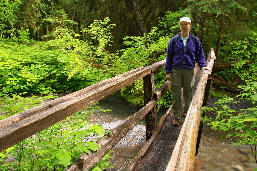 Woman hiking on wooden bridge over Barnes Creek, Olympic National Park, Olympic Peninsula, Clallam County, Washington, USA
