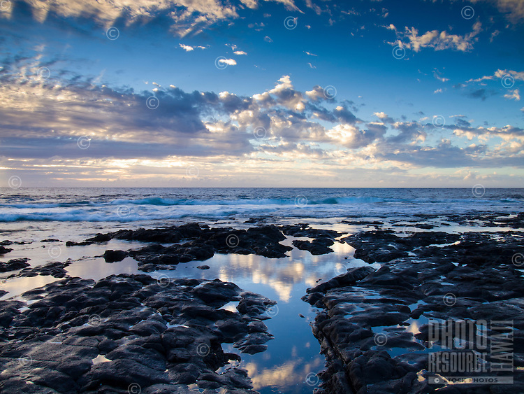 A beautiful blue sunset is reflected in the tide pools along the coastline of Keahole Point, Big Island.