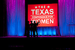 The camera crew on stage in silhouette at the Texas Conference for Women