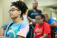 """College student Katherine Cabral (left), 20, of Chelsea, Mass., listens as Ayanna Pressley speaks at an event put on by Chelsea Black Community at the Chelsea Senior Center in Chelsea, Massachusetts, USA, on Wed., June 27, 2018. Pressley is running in the Democratic primary Massachusetts 7th Congressional District against incumbent Mike Capuano. Pressley is currently serving as a member of the Boston City Council, and is the first woman of color elected to the Council. Cabral is a volunteer for Pressley's campaign and says she will soon be canvassing for the candidate. """"I realized as a youth, I have a power to make a change,"""" Cabral said."""
