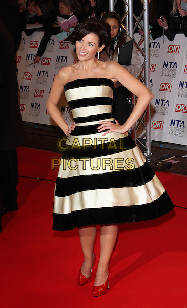 DANNII MINOGUE.The 15th National Television Awards held at the O2 Arena, London, England. .January 20th, 2010 .NTA NTAs full length black white strapless bold stripes striped red patent platform shoes hands on hips.CAP/ROS.©Steve Ross/Capital Pictures.