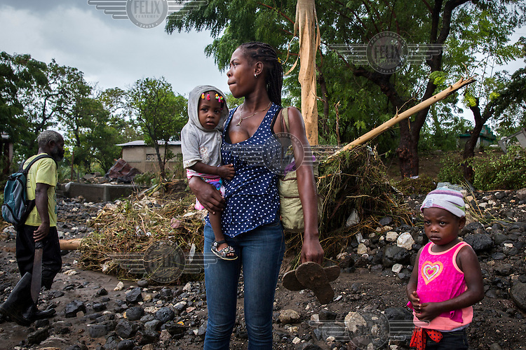 A woman and her children stand on the bank of La Digue River. Following the collapse, during Hurricane Matthew, of a bridge people were forced to wade across the water course. The downfall of the bridge meant emergency responders where unable to reach the worst hit southwestern peninsula of the island. Hurricane Matthew, the first category 5 Atlantic hurricane since 2007, hit the island on 4 October 2016. Winds of up to 230km/h (145mph) tore across the worst affected areas, mainly in the south of the island, killing around over 1,000 people and leaving hundreds of thousands in need of assistance.