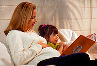Pregnant Hispanic woman reads to daughter