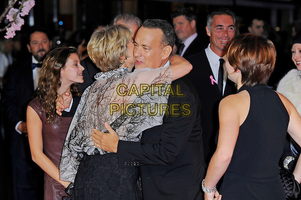 Emma Thompson and Tom Hanks<br /> attending the 57th BFI London Film Festival Closing Night Gala World Premiere of 'Saving Mr Banks', Odeon Cinema, Leicester Square, London, England. <br /> 20th October 2013<br /> half length black suit beige grey gray white sheer blouse top arms around hug embrace <br /> CAP/MAR<br /> &copy; Martin Harris/Capital Pictures