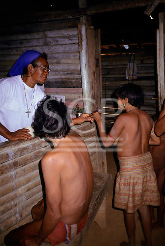 Roraima, Brazil. Sister Irma Florenca dispensing medication to Yanomami malaria victims at health post.