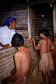 Roraima, Brazil. Sister Irma Florenca dispensing medication to Yanomami malaria victims at health post.