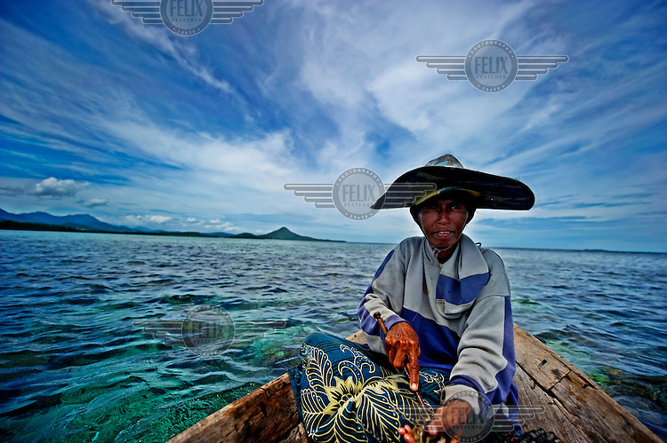 The wife of Bajau fisherman, Moen Lanke, shucks the clams he is bringing to the surface, and lays them out on a wire mesh to begin preparing them as a meal, which she will cook at the back of their boat (Lepa Lepa). The Bajau (Bajo) Laut are an ethnic group of Malay origin, they have for centuries lived out their lives almost entirely at sea, plying a tract of ocean between Malaysia, the Philippines and Indonesia.