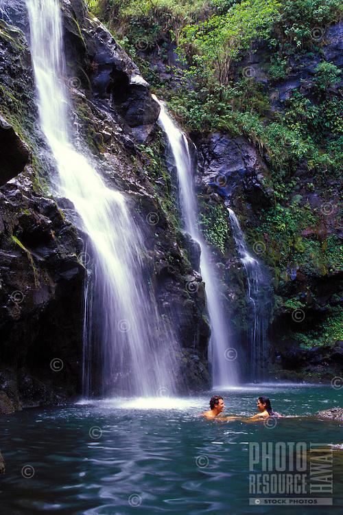 Young couple swim near a waterfall on the road to Hana, Maui.