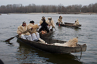 Locals celebrate the end of the winter during the old folk traditional festive of Busojaras crossing river Danube with boats in Mohacs, Hungary on March 06, 2011.