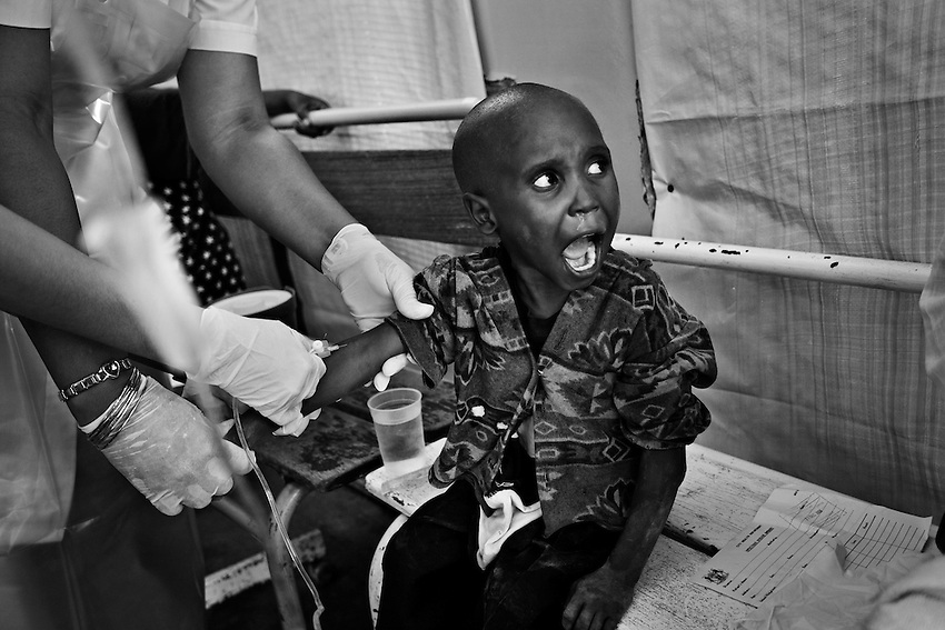 A Zimbabwean child infected with cholera has an IV needle inserted into his arm by a nurse at the Beatrice Infectious Diseases Hospital which is being used as a Cholera Treatment Clinic in Harare, Zimbabwe, Tuesday, December 23, 2008.