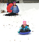 Gina Hartin (background) takes a video of her daughter Johanna Hartin, 6, as she slides down a slope at East End Park in Belleville on Saturday morning January 12, 2019. People were busy digging out -- and some were having fun -- after a major snowstorm hit the St. Louis metropolitan region. <br /> Photo by Tim Vizer