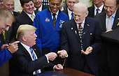 United States President Donald J. Trump, gives the pen to Apollo 11 astronaut Buzz Aldrin (R) after signing an Executive Order to reestablish the National Space Council in the Roosevelt Room of the White House in Washington, DC, on June 30, 2017. <br /> Credit: Olivier Douliery / Pool via CNP