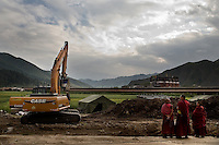 Monks look on as construction equipment digs up grassland in Xiahe, Gansu, China. Xiahe, home of the Labrang Monastery, is an important site for Tibetan Buddhists.  The population of the town is divided between ethnic Tibetans, Muslims, and Han Chinese.