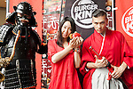 A customer poses for the cameras with Kuro Shogun (left) and Aka Samurai (right) during the new Burger King's red burgers launching event on July 3, 2015, in Tokyo, Japan. The two new burgers ''AKA SAMURAI CHICKEN'' and ''AKA SAMURAI BEEF'' use red buns and red cheese, colored by tomato powder and spicy red sauce and will be sold at Japanese branches until August. The AKA SAMURAI CHICKEN costs 540 JPY (4.39 USD) and the AKA SAMURAI BEEF costs at 690 JPY (5.61 USD). As a part of the promotion Burger King plans to launch two new black burgers on August 21st. (Photo by Rodrigo Reyes Marin/AFLO)