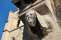 Sculpture of a nun below the corbel supporting a gargoyle, Collegiale Notre-Dame de Poissy, showing the Western bell tower and chapels of the North aisle, a catholic parish church founded c. 1016 by Robert the Pious and rebuilt 1130-60 in late Romanesque and early Gothic styles, in Poissy, Yvelines, France. Saint Louis was baptised here in 1214. The Collegiate Church of Our Lady of Poissy was listed as a Historic Monument in 1840 and has been restored by Eugene Viollet-le-Duc. Picture by Manuel Cohen