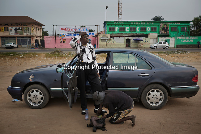 "KINSHASA, DEMOCRATIC REPUBLIC OF CONGO - July 18: Sapeur leader Papa Griffe has his shoes polished on a field on July 18, 2014, in Kinshasa, DRC. The word Sapeur comes from SAPE, a French acronym for Société des Ambianceurs et Persons Élégants or Society of Revellers and Elegant People and it also means, to dress with elegance and style"". Most of the young Sapeurs are unemployed, poor and live in harsh conditions in Kinshasa, a city of about 10 million people. For many of them being a Sapeur means they can escape their daily struggles and dress like fashionable Europeans. Many hustle to build up their expensive collections. Most Sapeurs could never afford to visit Paris, and usually relatives send or bring clothes back to Kinshasa. (Photo by Per-Anders Pettersson)"