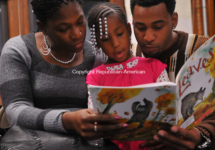 WATERBURY, CT- 10 November 2009 - 111009IP06- Lakeshia and Anthony Chapman of Waterbury read a book with their daughter Asia Chapman, 6, during a literacy event sponsored by the Waterbury Rotary Club and Literacy Volunteers of Greater Waterbury at the Waterbury Children's Community School on Tuesday, November 10, 2009. Attending families received a book to read and keep, a dictionary and a pasta dinner.<br /> Irena Pastorello Republican-American