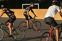 17 AUG 2014 - LONDON, GBR - A player from Triple Jay (in black) dribbles the ball up the court during the game against Partisans at the 2014 London Open Bike Polo tournament in Highbury Fields in London, Great Britain (PHOTO COPYRIGHT © 2014 NIGEL FARROW, ALL RIGHTS RESERVED)