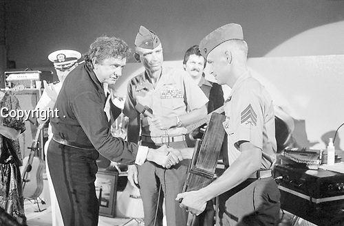 Entertainer Johnny Cash receives an award from a Marine sergeant during his performance for military personnel at the naval station, in 1987<br /> <br /> PHOTO : PH1 GARY RICE, USN