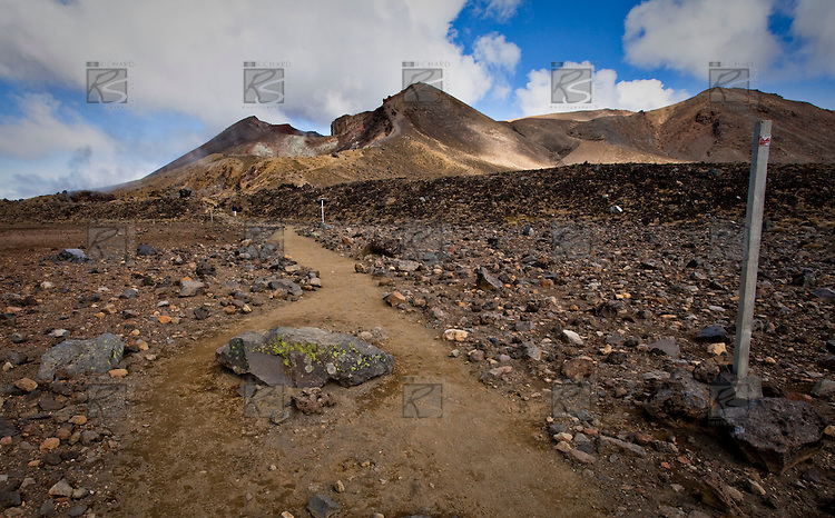 Considered one of the finest one day walks in the world, New Zealands Tongariro Crossing travels over the amazing volcanic alpine landscape of Mount Tongariro in the Tongariro National Park on the North Islands Central Plateau.. The 19.4 km walk takes you up the Mangatepopo valley to the Mangatepop saddle before crossing South Crater which lies between Mount Tongariro and Mount Ngauruhoe..From South Crater it is uphill again to the highest point of the crossing, the dramatic Red Crater, with views for miles in good weather. As you descend  you are greeted with the spectacular view across Central Crater to Blue Lake and Lake Taupo in the distance as well the much photographed Emerald Lakes nestled below Red Crater..After crossing Central Crater the track then travels along a low ridge next to Blue Lake before starting the long descent down past Ketetahi hut and  hot springs to  Okahukura Bush and the end of the walk.