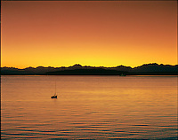 A small sailboat rests at it's moorage on calm sunset-colored waters. The Olympic Mountain range is silhouetted between orange tones of water and sky as a Washington State Ferry passes before them.....Photographed in 6X7 format on Velvia 50 film.
