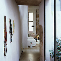 A narrow, white painted hallway leads to a sitting room. Strings of beads hang from hooks on the stone walls.
