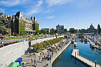 Crowds of tourist walk along harbor waterfront on summer afternoon, Victoria, British Columbia, Canada