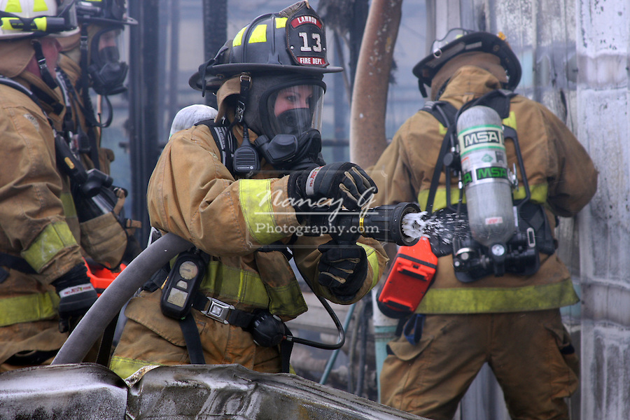 A woman firefighter from Lannon Fire Department putting water on a fire