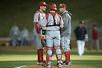 Sacred Heart Pioneers pitching coach Wayne Mazzoni (right) has a meeting on the mound with relief pitcher Julian Pedrouzo (left) and catcher Dan Fallacaro (20) during the game against the Wake Forest Demon Deacons at David F. Couch Ballpark on February 15, 2019 in  Winston-Salem, North Carolina.  The Demon Deacons defeated the Pioneers 14-1. (Brian Westerholt/Four Seam Images)