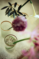 A detail of cut flowers standing in gold-rimmed glasses on a snow-dusted table