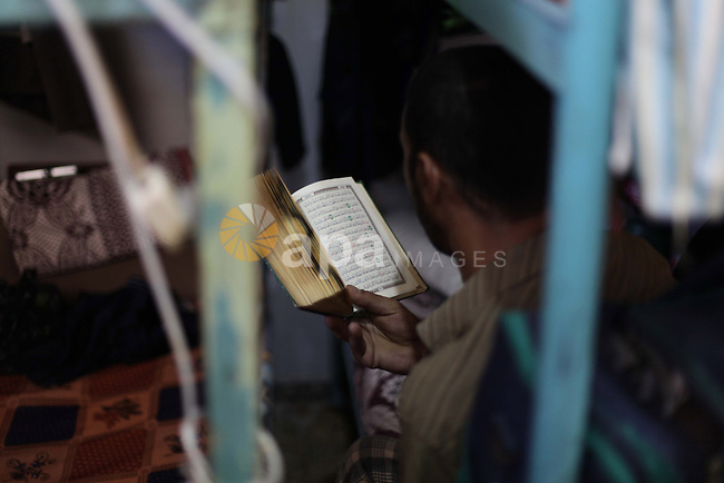 A Palestinian inmate reads holy Quran during the holy month of Ramadan at prison controlled by the Palestinian police in Gaza city on 28 July 2013. Palestinian police released more than 65 criminal inmates before the fasting month of Ramadan. Photo by Ashraf Amra