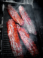 Four slabs of barbeque ribs cooking on gas grill. Photo from iPhone 3Gs