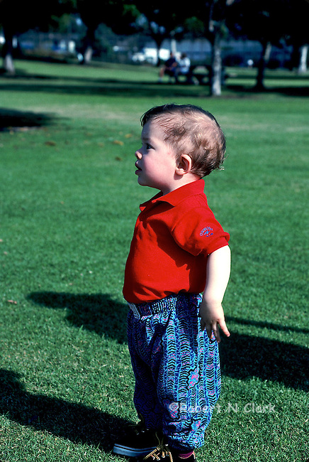 Young boy in park looking to the left with arms pulled back like he is in charge