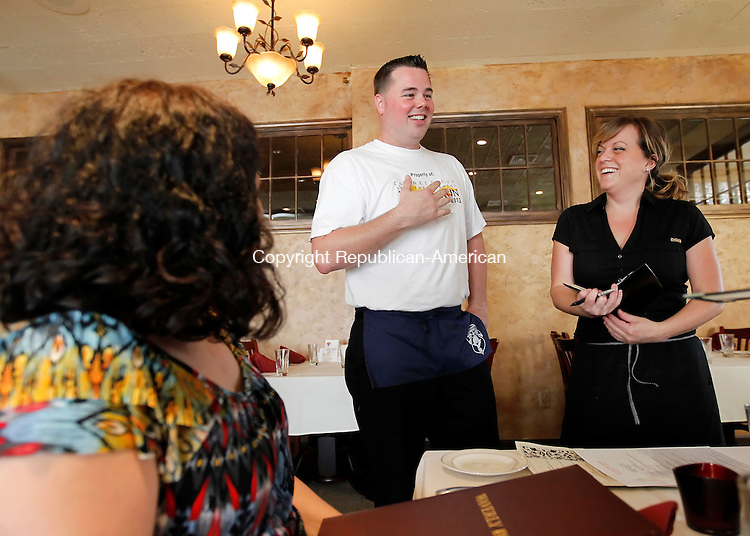 """Cheshire, CT-14 June 2012-061412CM01-  Cheshire Police Officer, Jay Bodell (center) and Nicole Kolinchak wait on Val Carbone (front left) and Rene Davidovich both of Cheshire (off frame) during a Tip a Cop event, at Waverly Tavern Thursday afternoon in Cheshire.  The annual fundraiser is held in conjunction with """"Dunk a Cop"""", held at the town fair later on this year and the Torch Run which was held last week.  Officers from the Cheshire Police Department volunteer to raise money where 100% of proceeds go to the Connecticut Special Olympics said Lorin Webber, the Department's coordinator for the CT Special Olympics.    Christopher Massa Republican-American"""