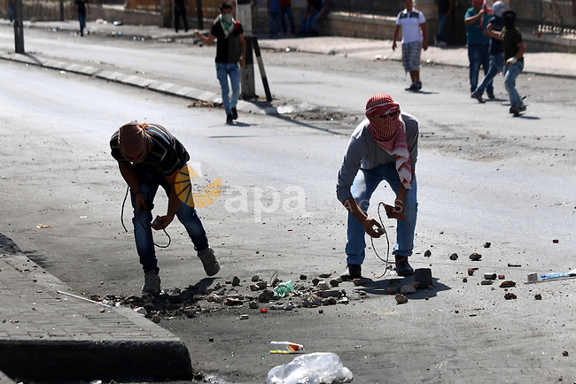 Palestinian protesters use slings to throw stones at Israeli troops during clashes in the West Bank city of Bethlehem October 14, 2015. Seven Israelis and 30 Palestinians, including children and assailants, have been killed in two weeks of bloodshed in Israel, Jerusalem and the occupied West Bank. The violence has been partly triggered by Palestinians' anger over what they see as increased Jewish encroachment on Jerusalem's Al-Aqsa mosque compound. Photo by Muhesen Amren