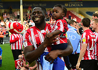 Lincoln City's John Akinde celebrates securing the League 2 Title<br /> <br /> Photographer Andrew Vaughan/CameraSport<br /> <br /> The EFL Sky Bet League Two - Lincoln City v Tranmere Rovers - Monday 22nd April 2019 - Sincil Bank - Lincoln<br /> <br /> World Copyright © 2019 CameraSport. All rights reserved. 43 Linden Ave. Countesthorpe. Leicester. England. LE8 5PG - Tel: +44 (0) 116 277 4147 - admin@camerasport.com - www.camerasport.com