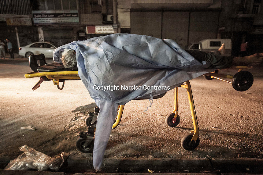 A body of a dead man lies on a trolley outside of a hospital as remains lonely due nobody has claimed for him after was killed by Assad's aircraft shelling in a residential neighborhood of Aleppo City.