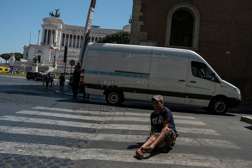 Rome, Italy, June 21, 2017. Un mendicante con problemi fisici attraversa una strada dissestata nel centro storico. A mendicant with physical problems crossing a bumpy road in the center of the city.<br /> Ad un anno dalla elezione a sindaco di Roma di Virginia Raggi, la condizione di degrado non accenna a migliorare.<br /> One year after the election as mayor of the candidate of M5S party, Rome is worsening day by day.