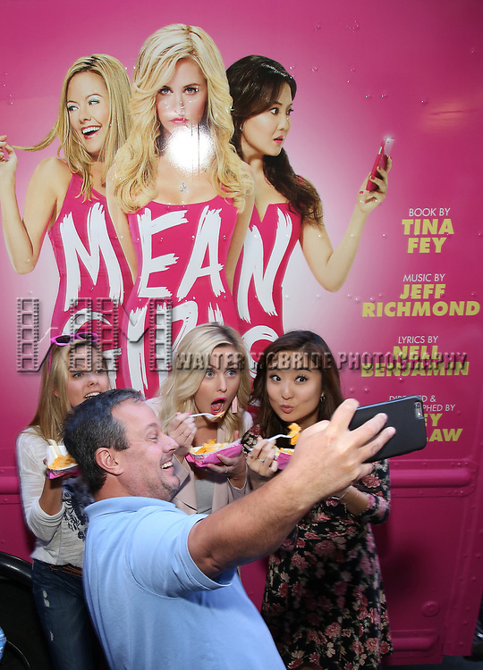 Fan poses with Kate Rockwell, Taylor Louderman and Ashley Park  from 'Mean Girls' cast visit the 'Mean Girls' themed Food Truck in celebration of 'Mean Girls' Box Office Opening Day on Broadway in Times Square on October 3, 2017 in New York City.