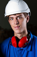 portrait of a happy engineer with safety helmet and earplugs