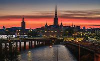 Röd natthimmel över Riddarholmen i Stockholm med Riddarholmskyrkan i siluett