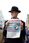 Bearded man in hat holding copy of The Socialist with headline 'Now let's bury Thatcher's legacy' at Ludgate Circus during the funeral of Margaret Thatcher, London, 17 April 2013.<br />