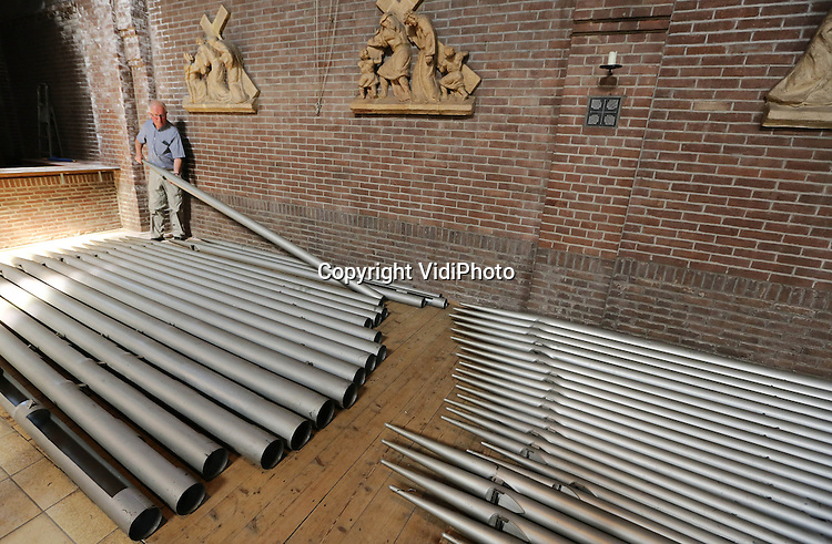 Foto: VidiPhoto<br /> <br /> ARNHEM - Vrijwilligers van de Heilig Hartkerk in Arnhem zijn woensdag aan het werk met de demontage van een 1600 pijpen tellend orgel (van de bekende orgelbouwer Pels) uit de Tweede Wereldoorlog. Het gevaarte krijgt volgend jaar een tweede leven in de Onze Lieve Vrouwe Visitatiekerk in Velp. De verhuizing kost zo'n 10.000 euro. Gelovigen (en sympathisanten) kunnen een pijp adopteren om zo het benodigde geld bij elkaar te brengen. De Heilig Hartkerk is inmiddels buiten gebruik. Van de oorspronkelijk zestien RK-kerken in Arnhem zijn er nog maar drie over. Iedere week moeten er door de ontkerkelijking in Nederland twee roomskatholieke en &eacute;&eacute;n protestantse kerk gesloten worden.