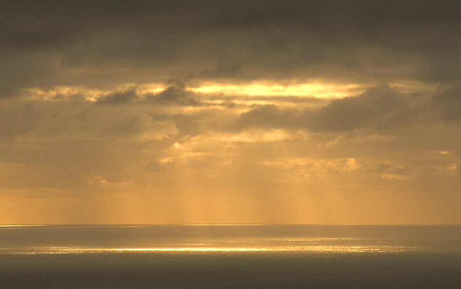 Sun beams breaking through clouds over Gulf of Saint Lawrence, Whale Cove, Cape Breton Island, Nova Scotia, Canada