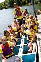 Dragon boat racing crew carefully debarking balancing on crooks of arms. Dragon Festival Lake Phalen Park St Paul Minnesota USA