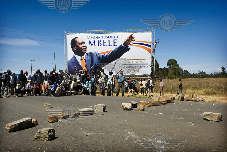 Supporters of the opposition Orange Democratic Movement (ODM), armed with machetes, bows and arrows, form a roadblock in a village 20km from Eldoret, next to a billboard promoting ODM leader Raila Odinga. Members of the Kikuyu tribe had been targeted in ethnic violence following protests against disputed election results. President Mwai Kibaki, a Kikuyu, was suspected of rigging the vote to retain power.