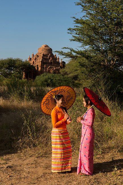 A model shoot with two young women in traditional dress and parasols with a small temple in the background in Bagan, Myanmar.